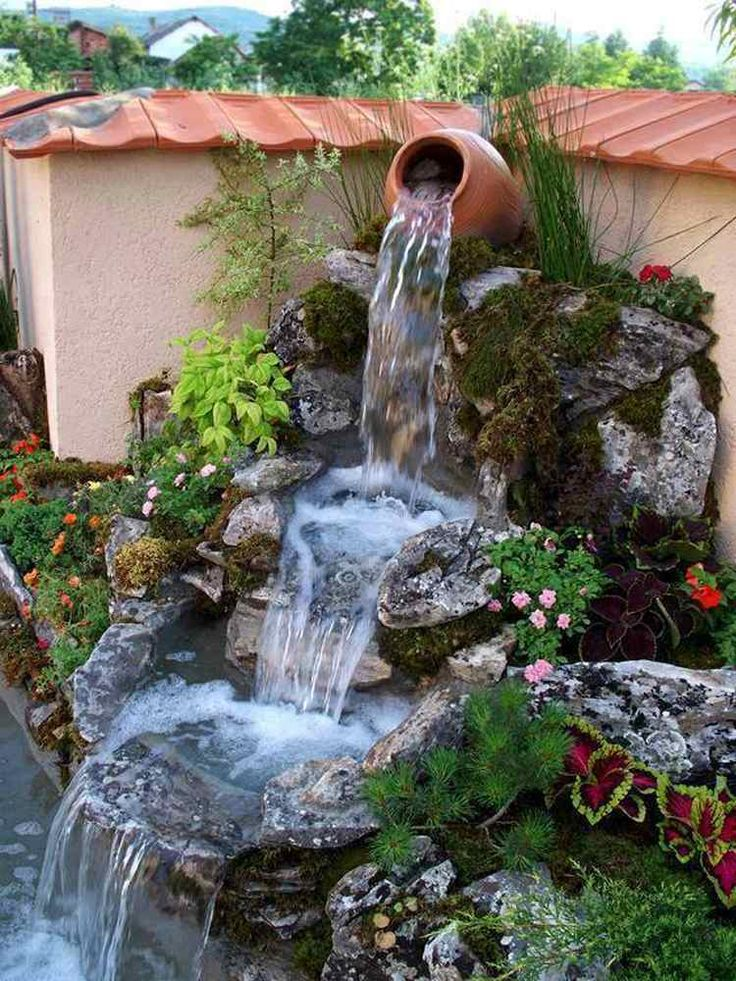 belle cascade de jardin en pierre naturelle décorée de plantes vivaces et de fleurs