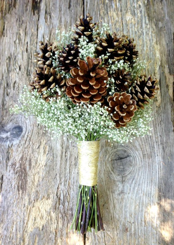 A simple winter wedding bouquet of pine cones and dried babys breath with your…