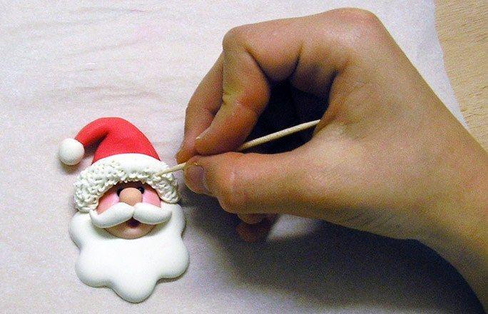Risvolto cappello Babbo Natale porcellana - Decorazioni albero Natale - Addobbi albero di Natale - Aggiungi una striscia di pasta bianca lungo il bordo del cappello rosso. Usa uno stecchino per renderlo simile a una pelliccia. Fai lo stesso sulla piccola pallina di pasta bianca da attaccare all'estremità del cappello...