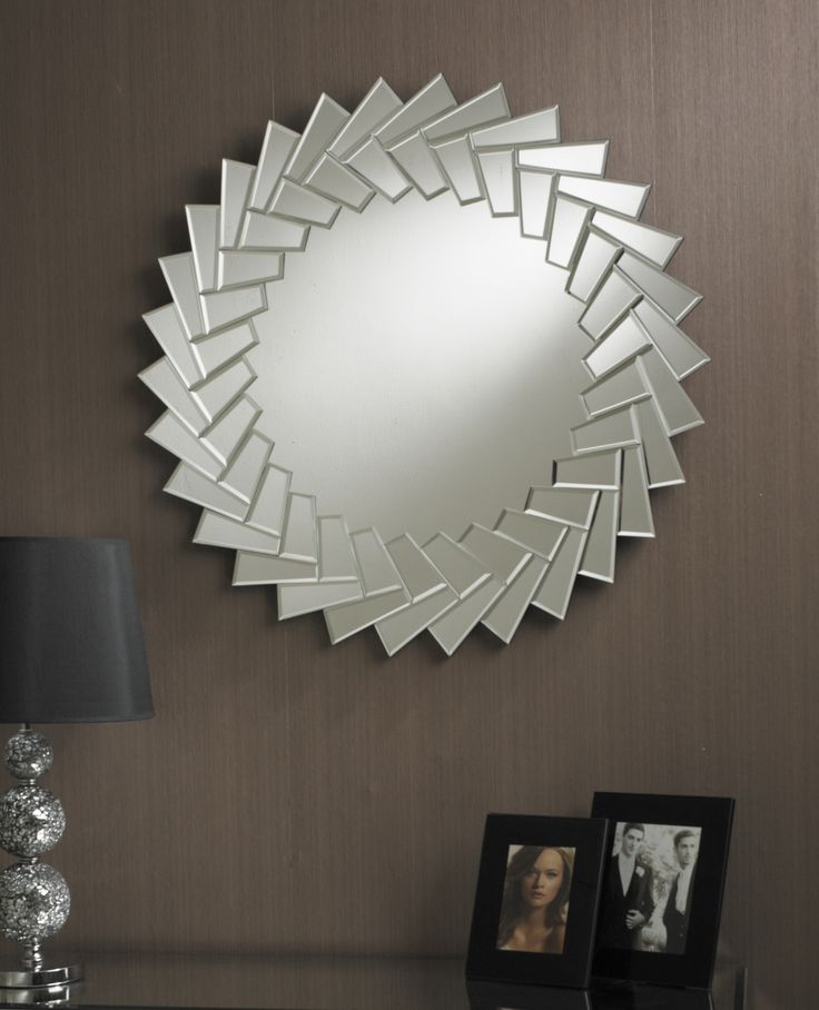 This is a modern round mirror which has an interesting border made up of overlapping square clear bevelled glass tiles. This gives a zigzag star-like shape to both the inside and the outside of the border. http://www.chicconcept.co.uk/round-mirrors/3235-round-mirror-with-border-of-tiled-square-glass-pieces-90cm-diameter-5055157622180.html