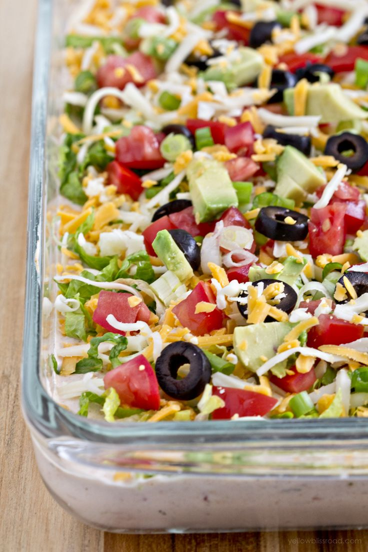 """This lightened up version of the classic 7 Layer Dip is the perfect appetizer for game day parties. Made """"skinny"""" with light cream cheese and fat-free greek yogurt, this dip will disappear quickly! About 15 years ago, I was living in my own apartment and was hosting my very first Tupperware party. I had recently …"""