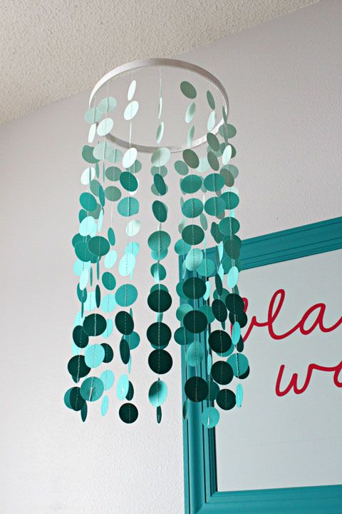 DIY mobile:  To make the mobile, we selected three shades of teal cardstock paper and used a paper punch to make stacks of circles in an ombré effect.  The ring at the top is the inside of an embroidery hoop which received a quick coat of white craft paint.