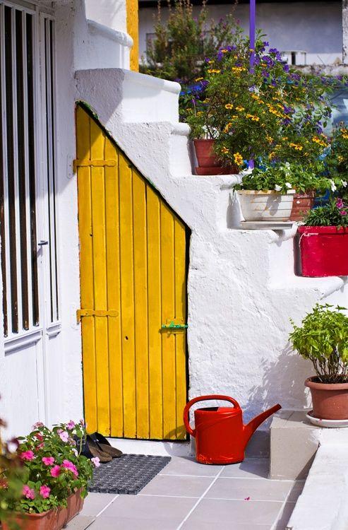 Yellow door with irregular shape highlights this garden corner.