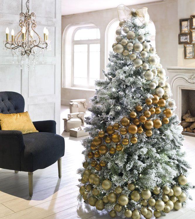 albero natale verde bianco decorazioni palline oro argento bianche lampadario antico vetro poltrona nera cuscino oro pacchi regali natalizi soggiorno salotto camino legna quadretti fiocco oro