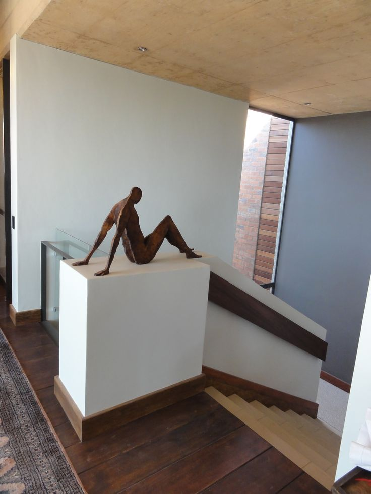 House Basson, in Pretoria, South Africa. This home is nestled on a hill in a Nature Reserve. The sloping site has a dual character, opening up to the views in the north while becoming more intimate and personal as you move southwards towards the nature reserve's green belt. Sculpt by Michael Heyns. Completed, 2012, Mathews and Associates Architects. Photo by MAAA