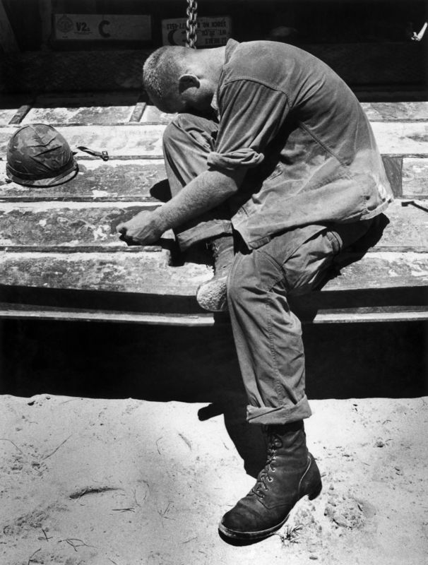 An exhausted marine sobs after carrying wounded and dead marines from a battle on An Hoa Island, South Vietnam, July 9, 1965 by Pulitzer Prize winner Eddie Adams.