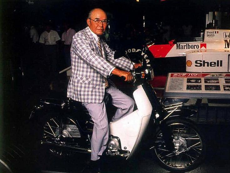 本田宗一郎さんがスーパーカブにまたがっている写真です。  角目のカスタムですね。珍しいショットです。1988年8月の写真だそうですから、  「スーパーカブ誕生30周年記念モデル」にまたがっているのですね。