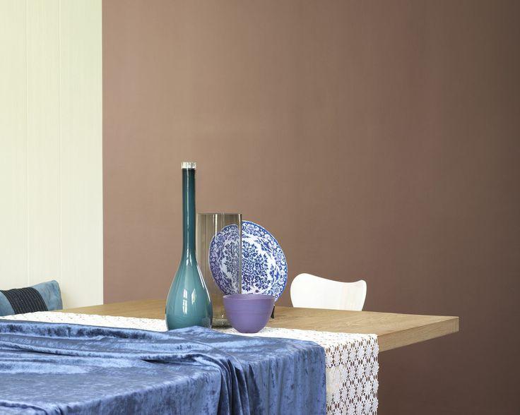 Redonnez vie aux teintes naturelles avec des bleus lumineux. Le mur marron et la table en bois de cette salle à manger prennent vie grâce aux différentes nuances de bleu des accessoires.