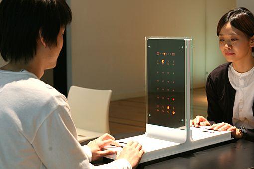 ICC ONLINE | アーカイヴ | 2007年 | オープン・スペース 2007 | アート&テクノロジー  これは二人が対面して競い合う対戦型ゲームのような作品です.中央に直立したスクリーンを介しているため,相手のスクリーンを見ることはできません.お互いが自分の側のスクリーンだけを見てゲームを行ないます.共通のゲームに興じる二人のプレーヤーの間には,互いに共通のコミュニケーションが成立しているように見えます.しかし,あたかも対戦しているように見える二人は,実際には一方が月面に着陸船を着地させるのに対してもう一方はキューピッドがハートを射抜く,というように異なる内容のゲームを,同じプログラムを介して行なっています. たとえば対話において,同じことについて話しているつもりがじつは互いに違うことについて話をしていた,ということがあるように,この作品では,そうしたコミュニケーションにおけるズレをゲームの形を借りて表現しています.そのような時に感じる文脈のおかしさを二人のプレーヤーの反応の中に見いだすことができるでしょう.