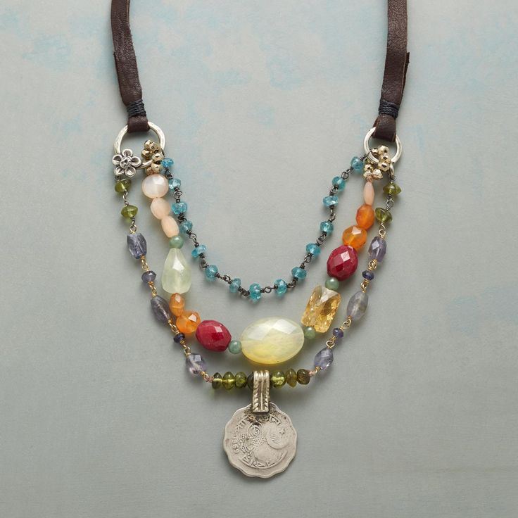"HIGH MEADOW NECKLACE -- Up high in the mountains, wildflowers bloom in hidden meadows. Capture that beauty in a tiered necklace of apatite, carnelian, iolite, peach moonstone, ruby, aventurine, peridot and citrine. Pewter charms, sterling silver chain. Adjustable with leather ties. USA. Exclusive. 24""L."