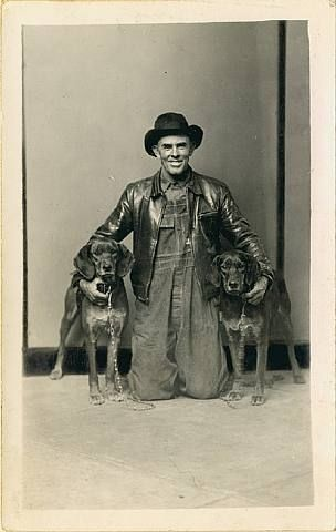 Mike Disfarmer, Untitled [Man in leather jacket kneeling with arms around his two hunting dogs, in front of striped background]: