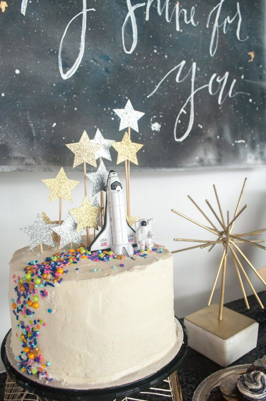 Love You to the Moon and Back monochrome space party hosted by @goldngrasses. An out of this world party with a modern chic vibe. Rocket cake with star glitter topper and Dainty Sprinkle Co Chasing Rainbows mix