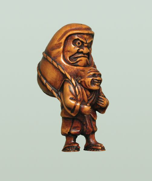 A boxwood netsuke of a man in porter's garments carrying a huge Daruma that is lashed on his back with a double rope. He appears to be enjoying the novelty of his task. The Daruma, however, is less than amused, preferring the comfort of terra firma. Despite its top heavy appearance, the carving is ingeniously balanced to stand perfectly. Signed Gyokuzan.  Height: 5.3 cm