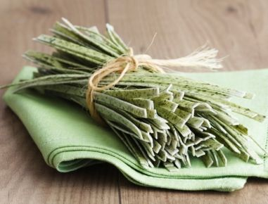 Für die Bärlauchnudeln die Bärlauchblätter mit kaltem Wasser abspülen, trocken schleudern und fein schneiden. Mit 1 TL Olivenöl und etwas Wasser
