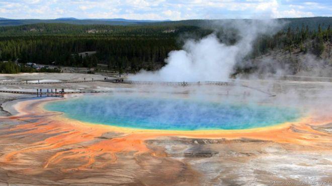 Suối vạn hoa Grand Prismatic, Mỹ. Suối Prismatic Spring sặc sỡ nhiều màu sắc là suối nước nóng lớn nhất ở Công viên Quốc gia Yellowstone của Mỹ. Suối rộng 90m và sâu trên 50m. Nơi đây tập trung nhiều khoáng chất, khiến tụ nhiều dải màu sắc từ đỏ tới xanh, được tạo thành từ các nhóm vi khuẩn ưa nhiệt khác nhau ở mỗi dải màu. Phần trung tâm có màu xanh lam rực rỡ là nơi cực nóng, với nhiệt độ lên tới 87 độ C.