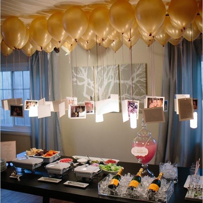 nfla globos con helio para que suban hasta el techo, imprime las mejores fotos que tengan juntos y con una perforadora hazles un pequeño hueco en la parte de arriba. Con los listones de los globos amarra las fotos y coloca los globos sobre la mesa de bebidas o comida. De esta manera todos los invitados podrán verlas y recordar, junto con ustedes, grandes momentos.