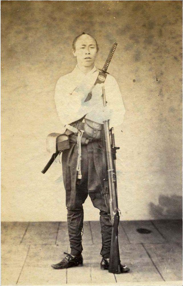 A Samurai posing with Musket and a Katana on his back by Ueno Hikoma, 1860s.