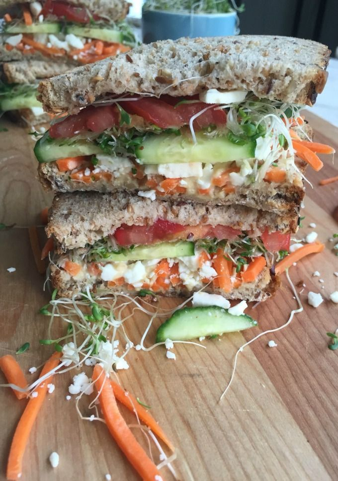 Mediterranean Veggie Sandwich  loaded with hummus and feta cheese, fresh vegetables and topped with sprouts. You won't miss the meat with this sandwich.