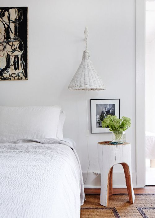 Peaceful white bedroom with white whicker pendant and painted carved stump side table.