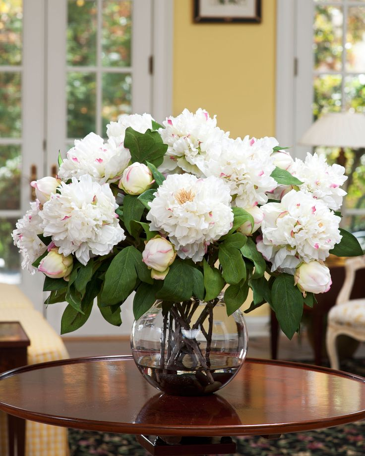 "Peonies have long been a favorite to bring in from the garden and can  now be an everlasting beauty in your home minus the black ants. This  silk beauty is arranged in an 8"" diameter bubble ball vase and our  crystal clear acrylic water, making this a definite ""Show Off""  centerpiece that is sure to bring a smiles to all who pass by. Available  in two popular colors."