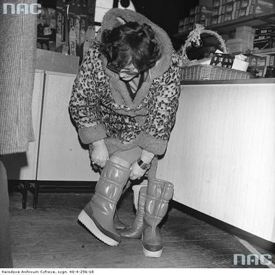 Opis obrazu: Stoisko ze sprzętem sportowym i obuwiem w Hali Gwardii. Klientka mierzy obuwie zimowe. Data wydarzenia: 1979-12