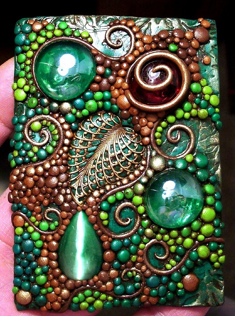 Chris Kapono - ACEO made of polymer clay in various shades of green and brown accented with a solid brass filigree leaf, glass gems and a catseye cabochon.  It reminds me of a woodland scene with droplets, leaves, tendrils and a shiny red berry.