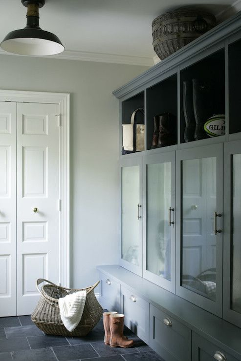 Gorgeous mud room with gray built-in cabinets with storage bench and cubbies framing frosted glass cabinet doors accented with nickel hardware.
