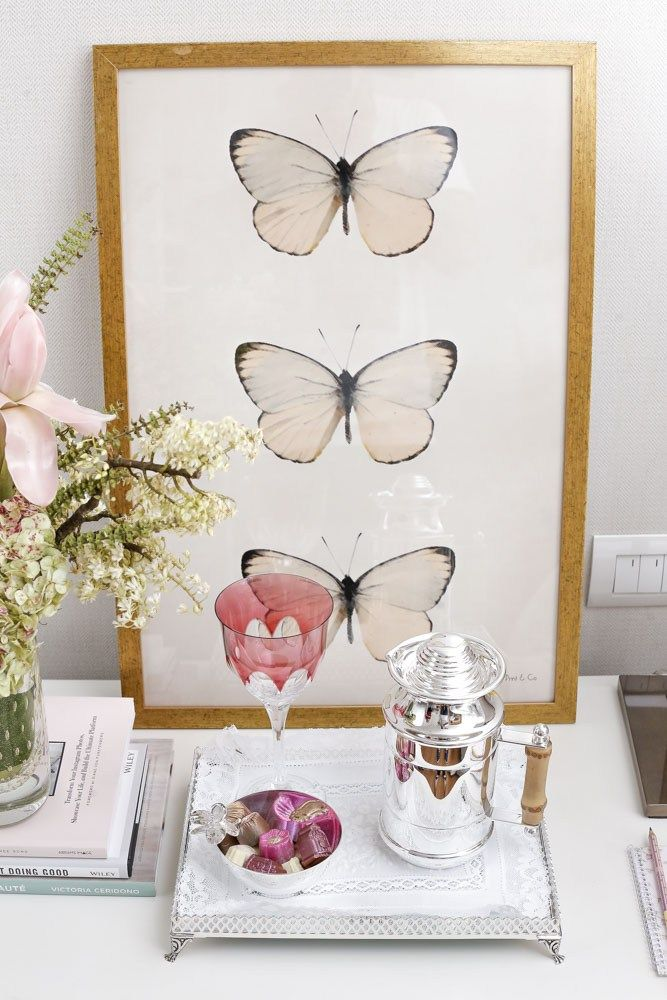 Para decorar cada lado da cama, dispomos os quadros de borboleta na cor offwhite da Theodora Home.