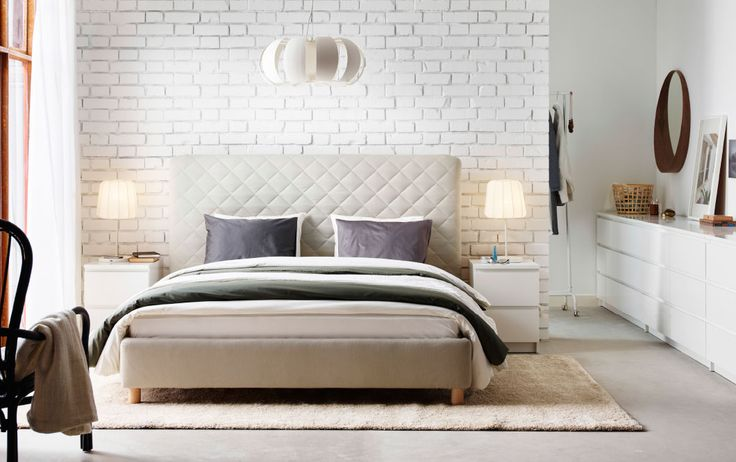A large white bedroom with a beige king size bed with an upholstered headboard…