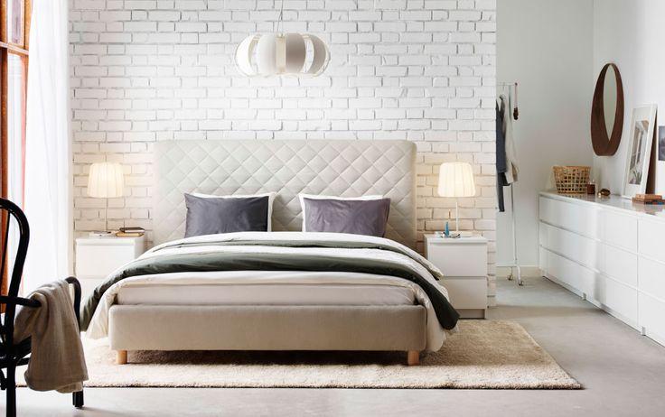 Veľká biela spálňa s béžovou posteľou s čalúneným čelom postele a bielou komodou použitou miesto nočného stolíka.