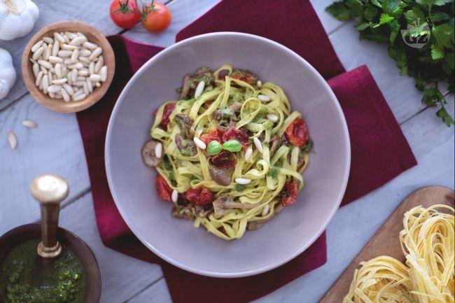 Le tagliatelle con pomodorini confit, chiodini e pesto sono un primo piatto molto ricco con un saporito condimento al pesto, funghi e ciliegini.