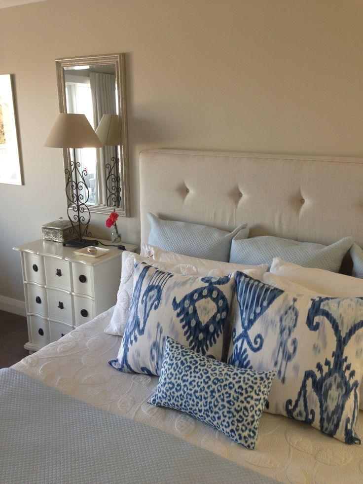 Upholstered bedhead in Belgium Linen with Ikat cushions and white quilt by Ornella Botter Interiors.