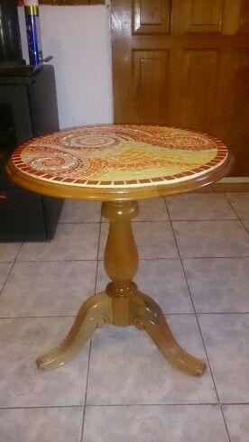 Mesa de madera Rauli,  pulida y barnizada. Cubierta decorada con mosaico de cerámicas y vidrio, cortados y pulidos, y una película de vidrio líquido.