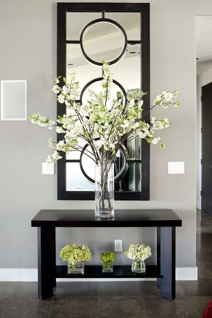 Bold yet simple entryway. Dark wood table accented by contemporary mirror draws the eye in.