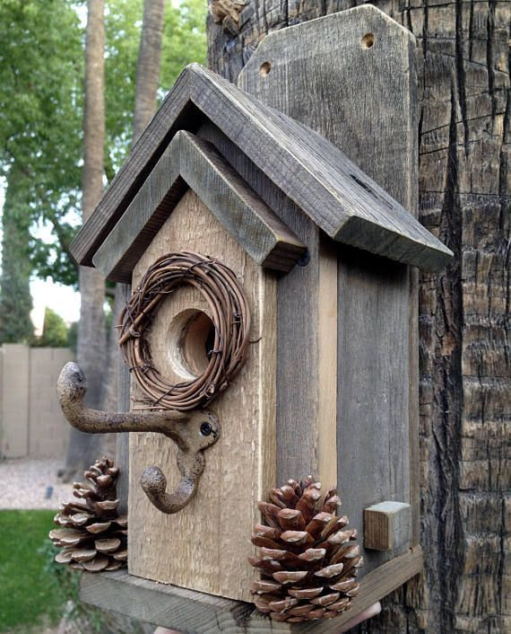 Here is a classic, rustic style that is easy to clean, and easy to mount. Two screws (included with your purchase) can easily attach this charming bird house to a tree or post. Made completely from rustic wood and decorated with real pinecones from our yard, plus a wreath around #birdhouses #buildabirdhouse #birdhouseideas