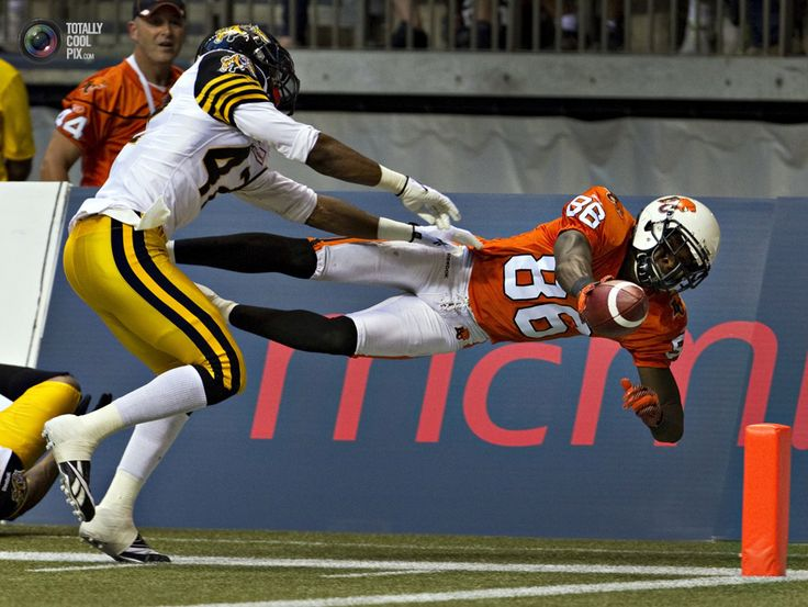 BC lions wide receiver Taylor dives for the goal line as Hamilton Tiger-Cats defensive back Brown moves in during CFL football game in Vancouver. ANDY CLARK/REUTERS