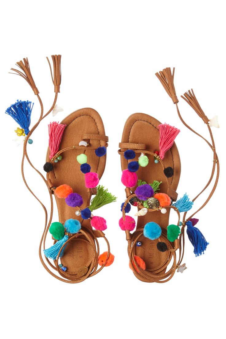Pom Pom Wrap leather gladiator sandals with colorful pom pom, tassel, and lucky charm trim.
