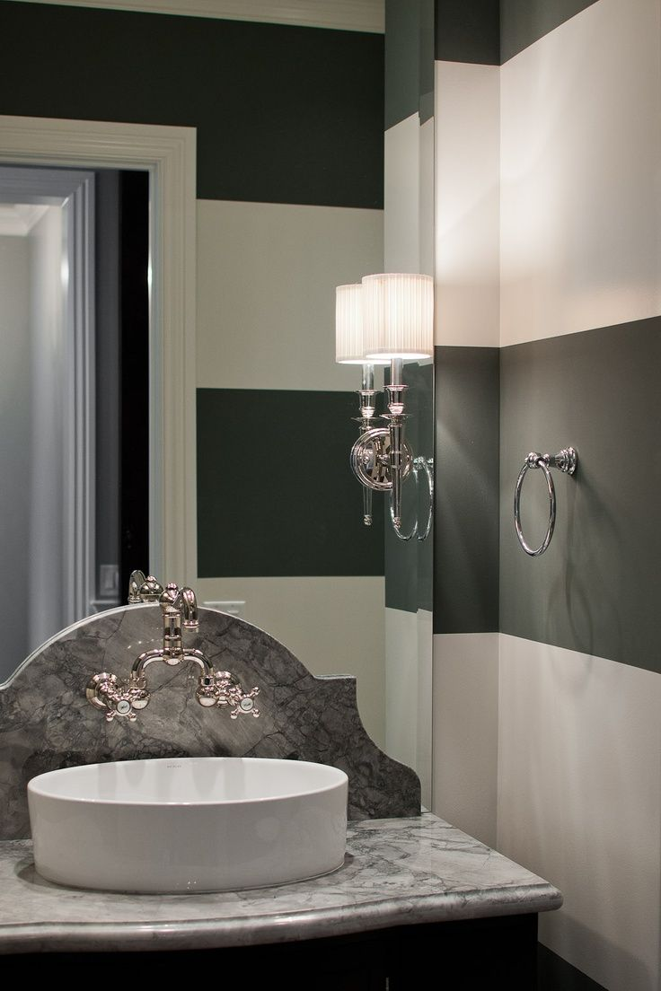 chic bathroom boasts black and white striped walls lined with a black washstand topped with gray quartzite lined with an oval vessel sink situated under a