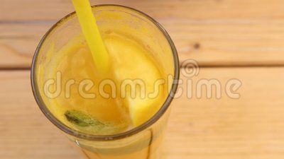 Glass with lemonade mixed with a straw.