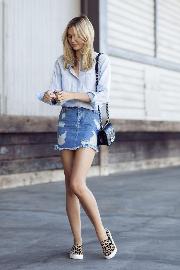 20 Modern Ways to Style a Denim Skirt for Spring - Tula Vintage in a chambray shirt, distressed denim skirt, and leopard print slip on shoes