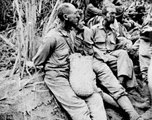 Prisoners on the march from Bataan to the prison camp, May 1942. (National Archives). It is hard not to notice the look of sheer hatred on the on POWs face as he looks at a guard.