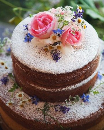 A naked almond cake with powdered sugar was topped with flowers.