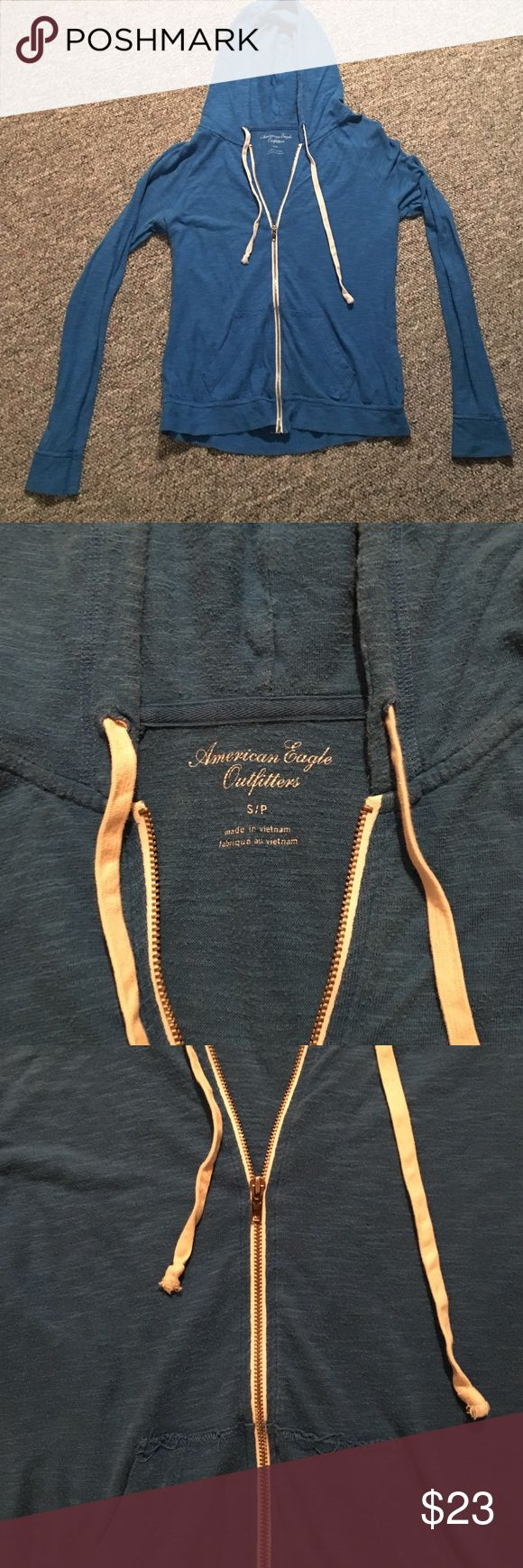 Blue zip up with hood. Light weight ocean blue zip up hoodie with white drawstring and zipper outline accents. Front pockets with small logo. American Eagle Outfitters Tops Sweatshirts & Hoodies