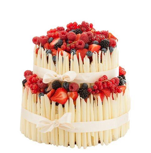 Speciální dort 09 Dvoupatrový dort, o rozměrech 18 cm a 24 cm, dozdobený hnědými či bílými ruličkami, čerstvým ovocem a saténovou stuhou.
