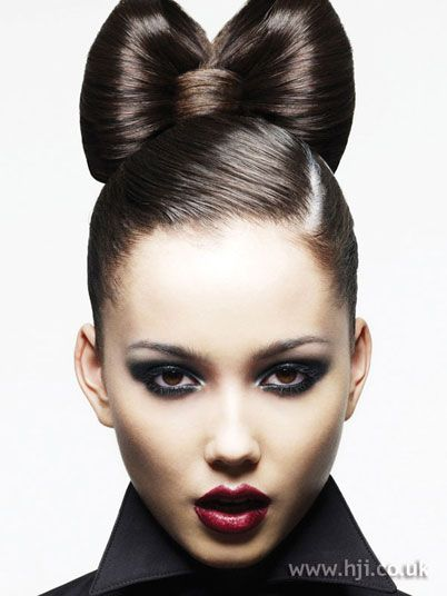 Classy Bow Updo - How it was done:   Hair was given a side parting and sleeked back into a high ponytail. The ponytail was then divided into two large sections that were back-combed to form volume and secured into a bow shape; and a third, smaller section that was positioned at the front of the bow to hide the grips and complete the shape.