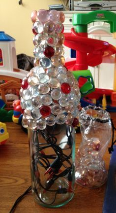Wine bottle, glass stones and lights - This would make such a cute Christmas decoration! Maybe orange and black for Halloween.... Or any other holidays!