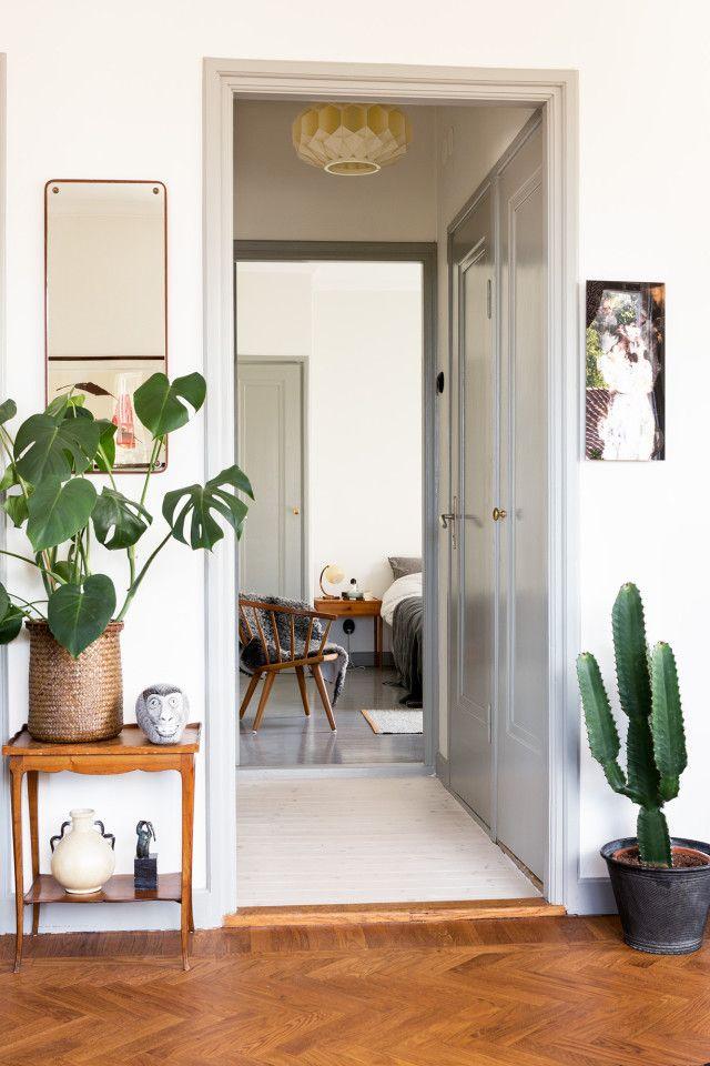 Det är inte bara konst som ett hem ska vara fullt av! Även gröna växter har en given plats hos Sandra. 70-talsklassikern Monstera finns det gott om, liksom snygga kaktusar. På det lilla bordet till vänster om dörren lite installationer.
