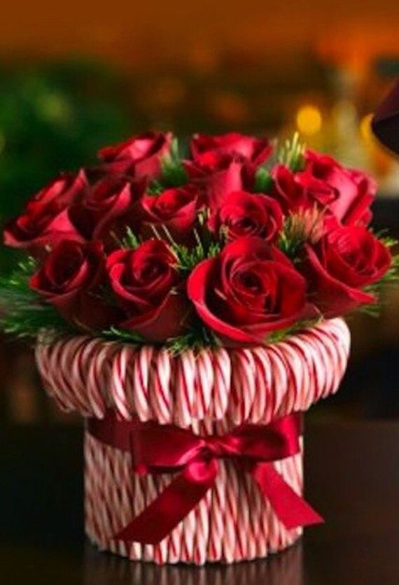 Stretch a rubber band around a cylindrical vase, then stick in candy canes until you can't see the vase. Tie a silky red ribbon to hide the rubber band. Fill with red or white roses or carnations.
