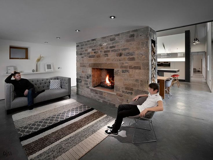 Fireplace Design Idea - 6 Different Materials To Use For A Fireplace Surround // An original stone fireplace surround has been kept in this renovated barn that's now a home.