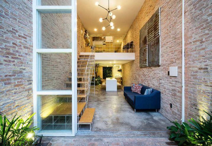Mattoni a vista per interni ed esterni di una casa in Vietnam A Ho Chi Minh una casa tropicale di mattoni rossi è resa moderna da soluzioni di esile metallo bianco.